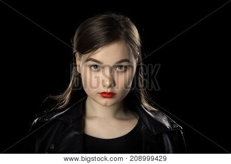 serious young female portrait on black background