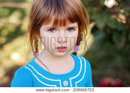 Closeup portrait of cute adorable little red-haired Caucasian girl child with blue eyes looking in camera. Happy childhood concept