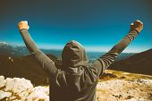 Achievement and triumph. Victorious female person standing on mountain top with arms raised in V. Achievement and accomplishment in life. Toned image. poster