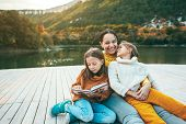 Family spending time together by the lake in autumn. Mom with her daughters reading book near the pond. Fall weekend in the open air. poster