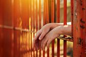 Female hands behind prison yard bars incarcerated captivated person in jail poster
