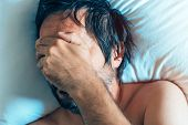 Morning depression and midlife crisis of a man in his 40s lying in bed in morning with symptoms like extreme sadness frustration anger and fatigue. poster