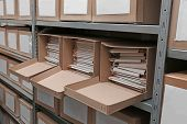 Cardboard boxes with documents on shelving unit in archive poster