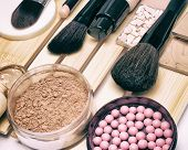 Makeup products and accessories to hide pigmentary imperfections, even out skin tone and complexion: concealer, foundation, powders, blush, make up brushes. Selective focus, retro toning poster
