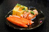 Grilled toro salmon sushi (sake nigiri) and mayonnaise top on rice Japanese rolled omelette (tamagoyaki) with shrimp eggs (tobiko) spring onion and imitation crab stick serve on black plate. poster