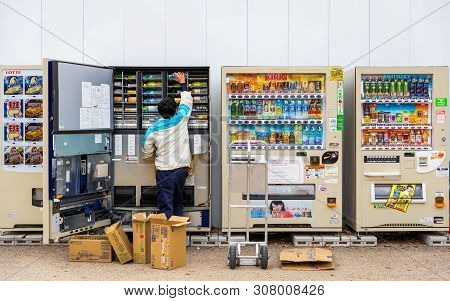 Osaka, Japan - November 22, 2018: Staff Fill Can And Bottle Of Beverage Into Vending Machines On Str