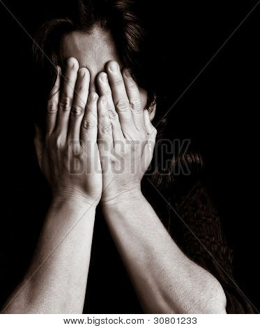 Desaturated portrait of a young woman crying and covering her eyes on a black background with space for text