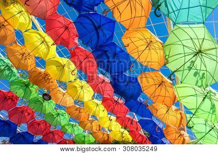 Colorful Umbrellas Hanging in the Air above the City Street. Colorful Summer Background. Rows of Color Umbrellas Protecting from Sunlight.