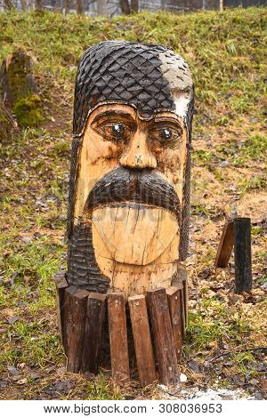 Wooden Sculpture In The Park In The Form Of A Male Face With A Mustache, Brown Wooden Sculpture