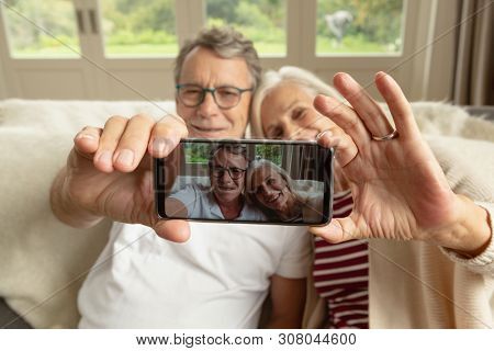 Front view of happy active senior Caucasian couple sitting on sofa and taking selfie in a comfortable home