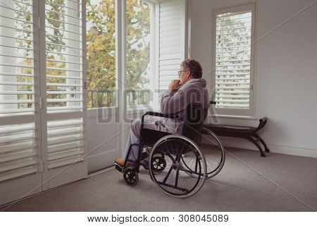Side view of thoughtful disabled active senior Caucasian man looking through window on wheelchair in a comfortable home