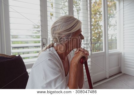 Side view of active senior Caucasian woman leaning on walking cane and looking away in a comfortable home