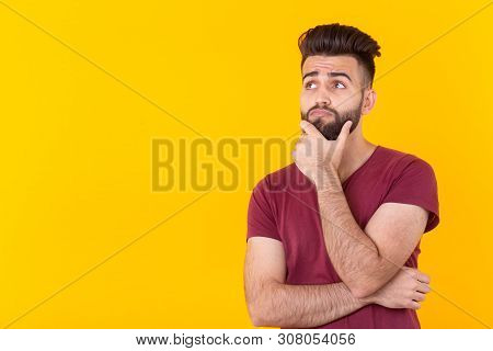 Apathetic cute young brunet man hipster is posing on a yellow background with copy space and thinking about something. Concept of unfulfilled dreams. poster