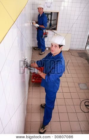 Electricians wiring a large tiled room