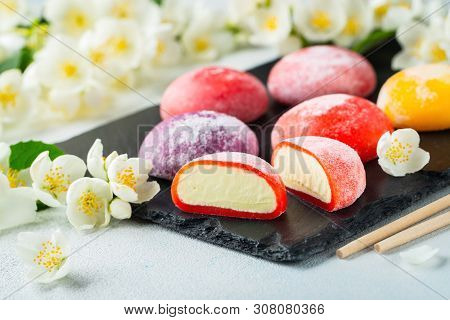Multi-colored Japanese Ice Cream Mochi In Rice Dough And Jasmine Flowers On A Concrete Blue Backgrou