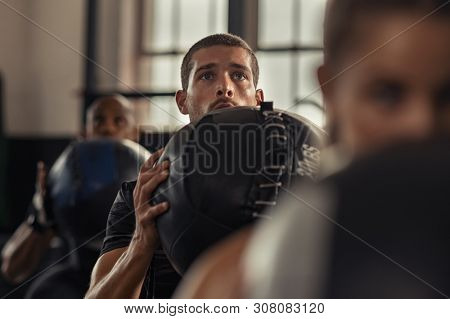 Portrait of young man lifting medicine ball with class in fitness center. Strong athlete doing strength training at gym. Guy holding heavy ball and doing squat exercise.