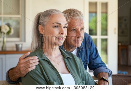 Old man embracing from behind his wife while sitting in front of house and contemplate future. Portrait of elderly husband and wife thinking together about the retirement. Vision and planning concept.