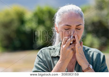 Senior woman having flu using nasal spray to help herself. Woman using a nasal spray at park for allergy. Ill mature woman with grey hair inhaling medicine against allergy.