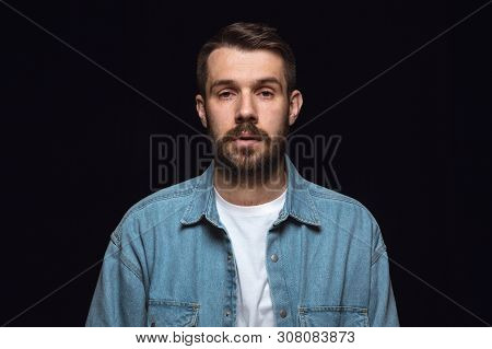 Close Up Portrait Of Young Man Isolated On Black Studio Background. Photoshot Of Real Emotions Of Ma