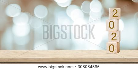 2020 Happy New Year Greeting Card, Wooden Cubes With 2020 Over Blur Bokeh Background With Copy Space