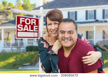 Mixed Race Young Adult Couple In Front of House and For Sale Real Estate Sign.