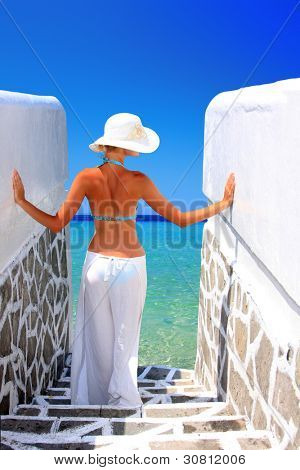 Glamour style photo of beautiful girl posing in summerhouse on beach.