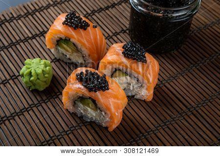 Sushi Roll Philadelphia With Salmon, Smoked Eel, Avocado, Cream Cheese On Black Background. Japanese