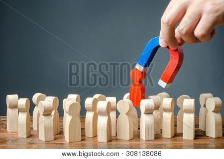 Businessman Pulls Out A Red Figure Of A Man From The Crowd With The Help Of A Magnet. Increase Team