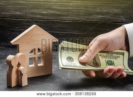 The Hand Of A Businessman Stretches A Wad Of Money To The Family Figures Near The Wooden House. Prov