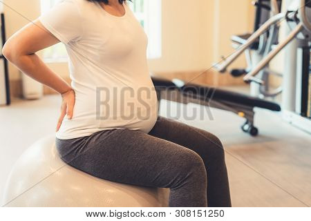 Active Pregnant Woman Exercise In Fitness Center.
