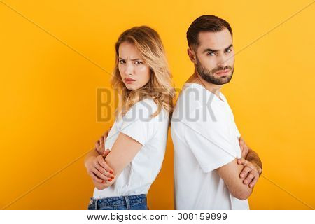 Image of confused couple man and woman in basic t-shirts frowning while standing back to back during fight isolated over yellow background