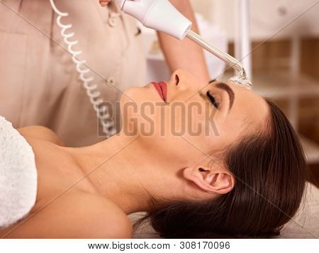 Facial treatment procedures darsenval. Close up of young woman with female beautician does face skin care stimulator. poster