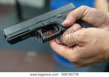 A Hand Of Man Practicing Firing Using A Glock Gun Model At The Shooting Range. Fire Glock Hand Gun.