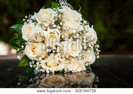 Bouquet Of Cream Roses On The Hood Of A Black Car