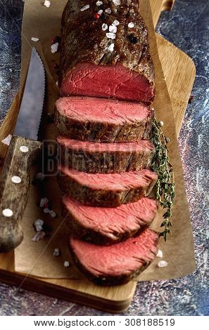 Roast Beef From Tenderloin A Large Piece Is Cut Into Pieces. A Large Portion Of Meat Served On A Woo