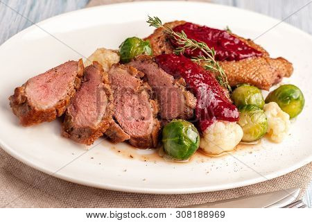 Roasted Duck Breast With Vegetable Garnish. The Meat Is Sliced Into Portions And Sprinkled With Cran