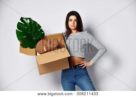 Upset disgruntled young attractive brunette girl holding a cardboard box full of things - plant, hat and others. She is dressed in jeans and a casual jersey. Concept relocation fees poster