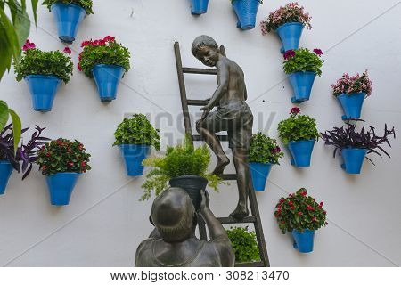 Cordoba, Spain - April 14th, 2019: Sculpture Made Of Bronze With A Child And His Grandfather Caring