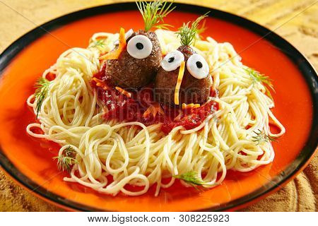 Creative Serving Healthy Kids Food with Noodles, Tomato Sauce and Meat Balls in the form of Funny Birds on Natural Ceramic Plate Close Up. Macro Photo of Healthy Kid Food for Children Main Menu