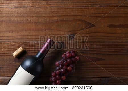 Wine Still Life: Overhead view of a Cabernet Sauvignon wine bottle on a dark wood surface with grapes and cork and copy space.