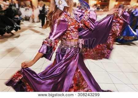Beautiful Gypsy Girls Dancing In Traditional Purple Floral Dress At Wedding Reception In Restaurant.