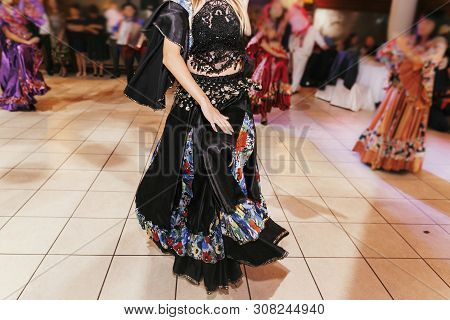 Beautiful Gypsy Girls Dancing In Traditional Black Floral Dress At Wedding Reception In Restaurant.