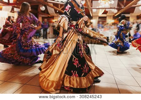 Beautiful Gypsy Girls Dancing In Traditional Colorful Clothing. Roma Gypsy Festival. Woman Performin
