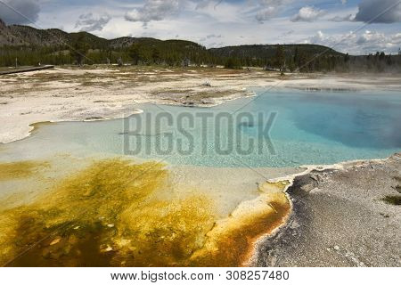 Geothermal Lake With Colorful Mineral Sediments In Yellowstone, Wyoming, Usa