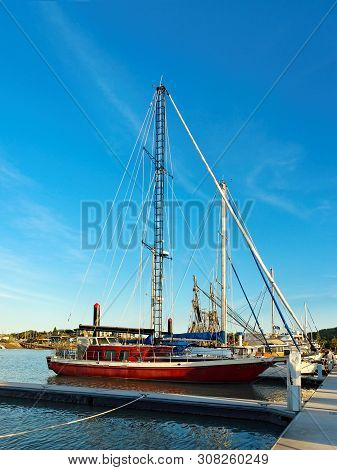 Blue Sky Nautical Marina Vista With A Docked Red Hull Sailing Yacht With A Very Unusual Custom Made