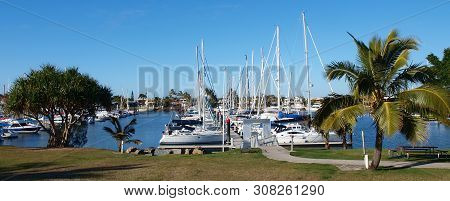 Landscape Panorama With Boats Berthed At A Tropical Waterfront Marina Including Palm Trees And Blue