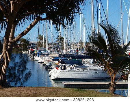Nautical Waterscape With Boats Berthed At A Tropical Waterfront Marina Including Palm Trees And Blue