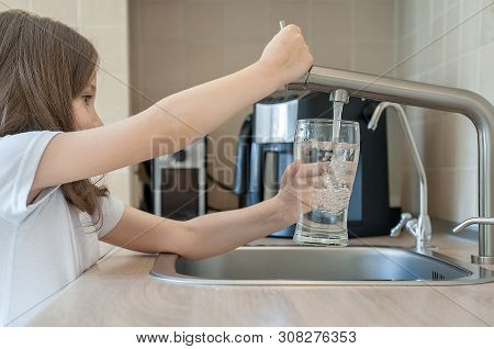 Portrait Of A Little Caucasian Baby Girl Holding A Glass Of Tap Clean Water. Kitchen Faucet. Cute Ki