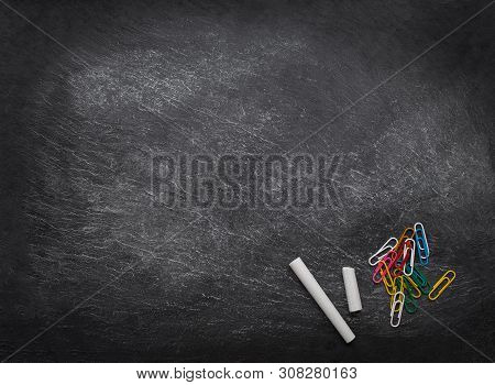 Back To School Background. Black Chalkboard With Chalk Pieces And Paper Clips. School Supplies. Flat
