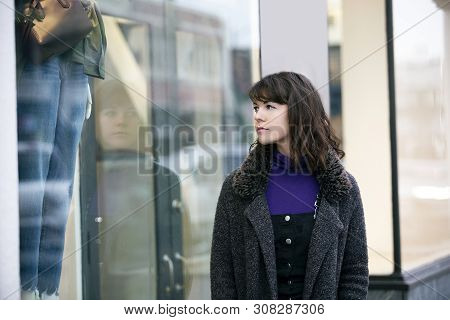 Woman Walking Outdoors In A City. She Is Window Shopping And Looking At A Store Sale Advertising Or